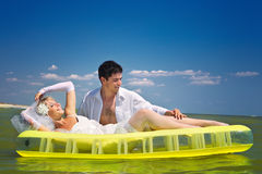 Newly-married couple enjoying on beach. A young and beautiful newly-married couple enjoying on an inflatable mattress has gone mad of pleasure Royalty Free Stock Images