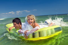 Newly-married couple enjoying beach. A young and beautiful newly-married couple enjoying on an inflatable mattress has gone mad of pleasure Stock Photo