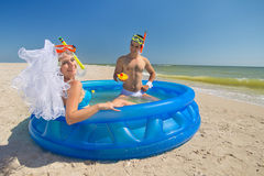 Newly-married couple enjoying on the beach. A young and beautiful newly-married couple enjoying on the beach in swimming pool Stock Photo