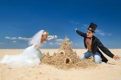 Newly-married couple enjoying on the beach. A young and beautiful newly-married couple enjoying on the beach near sandy castle at the sea edge Royalty Free Stock Photos