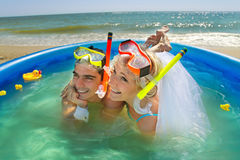 Newly-married couple enjoying on the beach. A young and beautiful newly-married couple enjoying on the beach in swimming pool Stock Image