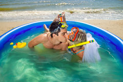 Newly-married couple enjoying on the beach. A young and beautiful newly-married couple enjoying on the beach in swimming pool Royalty Free Stock Images
