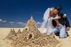 Newly-married couple enjoying on the beach. A young and beautiful newly-married couple enjoying on the beach near sandy castle at the sea edge Stock Images