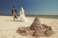 Newly-married couple enjoying on the beach. A young and beautiful newly-married couple enjoying on the beach near sandy castle at the sea edge Stock Image