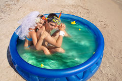 Newly-married couple enjoying on the beach. A young and beautiful newly-married couple enjoying on the beach in swimming pool Stock Images