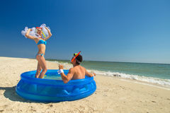 Newly-married couple enjoying on the beach. A young and beautiful newly-married couple enjoying on the beach in swimming pool Royalty Free Stock Photo