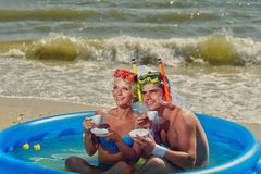 Newly-married couple enjoying on the beach. A young and beautiful newly-married couple enjoying on the beach in swimming pool with cups of coffee Stock Photography
