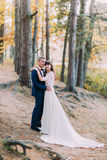 Newly married couple holding each other. Bride's long dress tail spreading on the forest ground Stock Photography