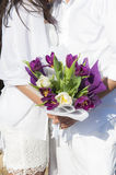 Newly married couple holding flowers Stock Photos