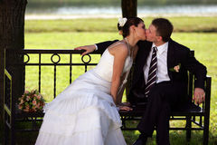 Newly married couple kissing. A portrait of a newly married man and woman, pictured after their marriage ceremony. They are both sat on a park bench in a Stock Photo