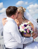Newly married couple kissing against blue sky Stock Image