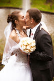 Newly married couple kissing against fountain Royalty Free Stock Images