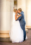 Newly married couple kissing against old column Royalty Free Stock Image