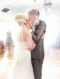 Newly married couple kissing on dance floor Stock Photo