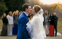 Newly married couple kissing in front of happy guests at park Stock Image