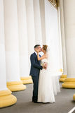 Newly married couple kissing at old white columns Royalty Free Stock Photography