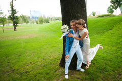 Newly married couple laughs. Happy newly married couple laughs on a green lawn Stock Image