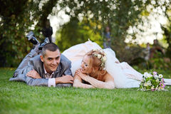Newly-married couple lies on a grass Royalty Free Stock Image