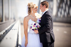 Newly married couple looking at each other on bridge Stock Photography