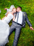 Newly married couple lying on grass and kissing Stock Photo