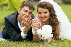 Newly married couple lying on grass and looking at wedding rings Royalty Free Stock Photo