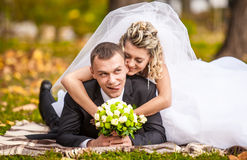 Newly married couple lying on grass in park and having fun Stock Images