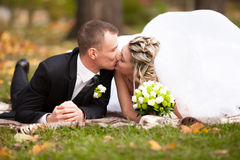 Newly married couple lying on grass at park and kissing Stock Photos