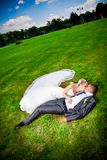 Newly married couple lying on grass at park Stock Photography