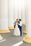 Newly married couple posing between high columns at sunny day Royalty Free Stock Photo