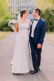 Newly married couple posing in sunny park at alley. Beautyful bride holding her bridal bouquet Stock Photography