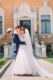 Newly married couple posing in sunny park at alley. Groom is holding elegant bride on his hands. Vintage building as background Stock Photos