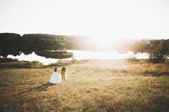Newly married couple running and jumping in park while holding hands Stock Photos