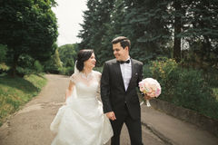 Newly married couple running and jumping in park while holding hands Royalty Free Stock Photo