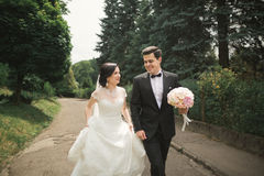 Newly married couple running and jumping in park while holding hands Royalty Free Stock Photography