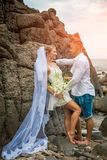 Newly married couple by the sea on their wedding day. Newly married couple by the sea rocky beach on their wedding day. Happy together Royalty Free Stock Photo