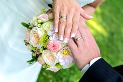 Newly married couple shows his rings on the bridal bouquet Royalty Free Stock Image