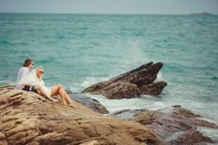 Newly married couple sit on rocky beach and look to sea. Vacation in Thailand Stock Images
