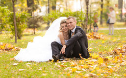 Newly married couple sitting on grass at autumn park Royalty Free Stock Photography