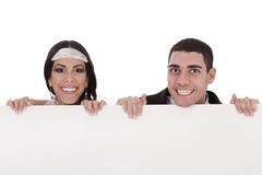 Newly married couple standing behind the board. In white background Stock Photography