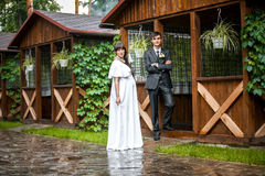 Newly married couple standing in wooden alcove in rainy weather Stock Image