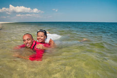 Newly-married couple swimming in sea Stock Photography