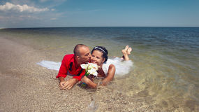 Newly-married couple swimming in sea Royalty Free Stock Image