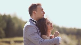 A newly married couple on their wedding day amongst the green nature next to the lake. They are together in the arms of stock video footage