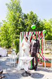 Newly married couple under wedding arch. Young newly married couple under wedding arch Royalty Free Stock Photography