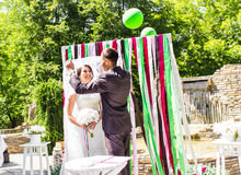 Newly married couple under wedding arch. Young newly married couple under wedding arch Royalty Free Stock Photo