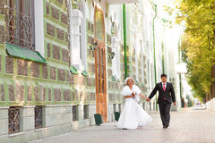 Newly married couple walk in the city  holding Royalty Free Stock Images