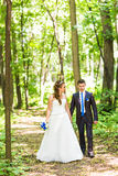 Newly married couple walk on park paths holding hands Royalty Free Stock Images