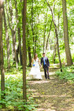Newly married couple walk on park paths holding hands Stock Images