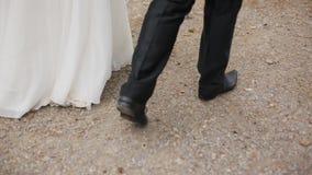Newly married couple walk on sidewalk. stock video footage