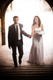 Newly married couple walking under ancient arch Royalty Free Stock Photography